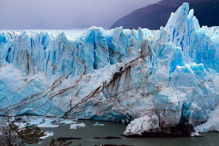 Patagonia. Fantastic lake and glacier Perito Moreno. On the surface of the glacier formed Calgaspors - penitent snow. The concept of exotic and extreme tourism
