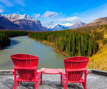 abraham: Two red comfortable loungers by the Abraham lake. Warm September in the mountains of Canada. Concept of ecological and active tourism