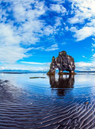 Il concetto di turismo estremo del nord. La famosa roccia Hvitserkur sotto forma di un enorme mammut. La costa nord dell'Islanda. Marea oceanica al tramonto Archivio Fotografico