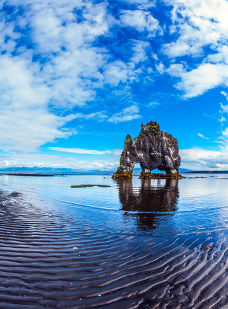 The concept of extreme northern tourism. The famous rock Hvitserkur in the form of a huge mammoth. The north coast of Iceland. Ocean tide at sunset Imagens
