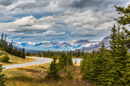 The road to distant snow-capped mountains in the Rockies of Canada. Rocks and lakes under flying clouds. Concept of active and ecological tourism Stock Photo