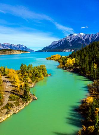 Setembro quente nas montanhas do Canadá. Lago requintado Abraham Reservoir com água turquesa. Na costa do lago, madeiras multicoloridas de outono. Conceito de turismo ecológico e ativo