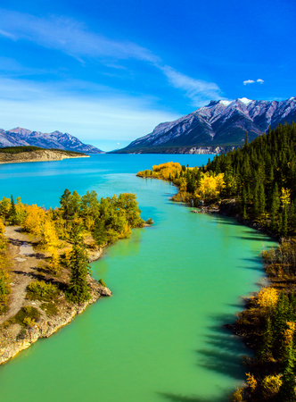 abraham: Warm September in the mountains of Canada. Exquisite Abraham Reservoir Lake with turquoise water. On coast of the lake autumn multi-color woods. Concept of ecological and active tourism