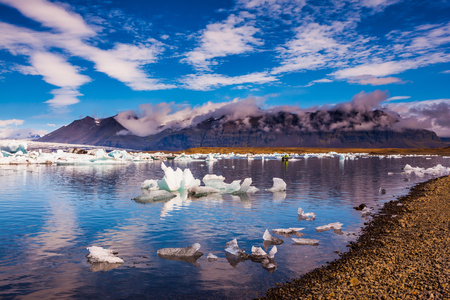 smooth: The ice floes and cirrocumulus clouds of lagoon Jokulsarlon, Iceland.  Cirrocumulus magically reflected in the smooth water of the lagoon. The concept of northern extreme tourism