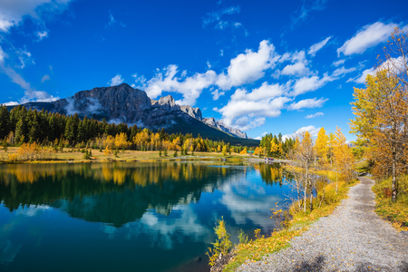 Canmore, near Banff Park. Path around the lake. The concept of hiking. Mountains and autumn aspens reflected in the water 版權商用圖片