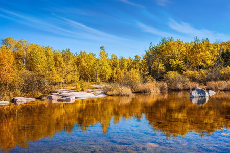 The Winnipeg River. Yellow autumn grass is reflected in the smooth water surface. Old Pinawa Dam Provincial Heritage Park. The concept of travel Around the World