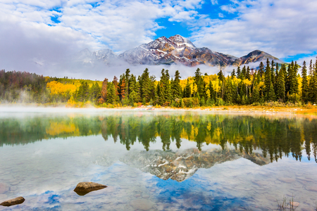Patricia Lake among the pines. The water reflects the peak of the Pyramid Mountain and the lush cumulus clouds. The concept of ecotourism