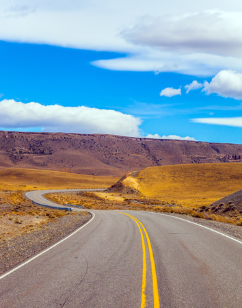 Sharp turn of the road in the Argentine prairie. Patagonia. Summer day in February. The concept of active and extreme tourism