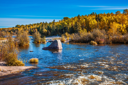 The concept of world tours. Warm autumn day. Foam water on the stones of the Winnipeg River. Old Pinawa Dam Park Stock Photo
