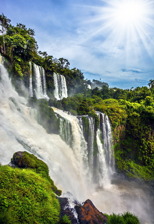 Waterfalls Iguazu, Argentina. The tropical sun illuminates the seething waters. Picturesque basaltic ledges form the famous waterfalls. The concept of active and exotic tourism Stock Photo