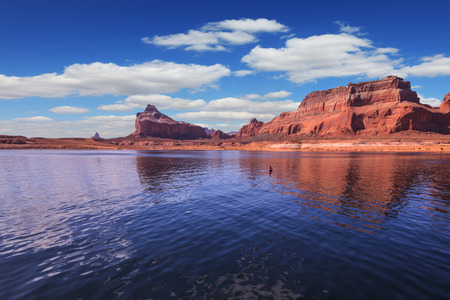 Scenic huge artificial water basin of the Colorado River, USA. Lake Powell is surrounded by magnificent sandstone hills. A boat trip on a sunny day