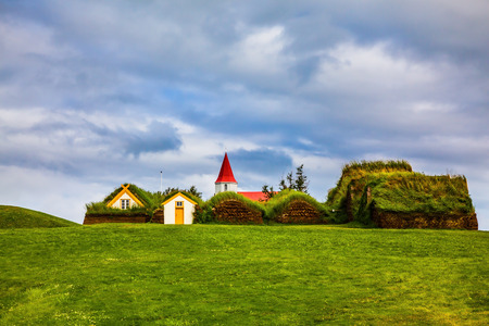 The village of houses covered with turf and grass. Church bell tower with red gabled roof. Ethnographic Museum-estate Glaumbaer, Iceland. The concept of the historical and cultural tourism
