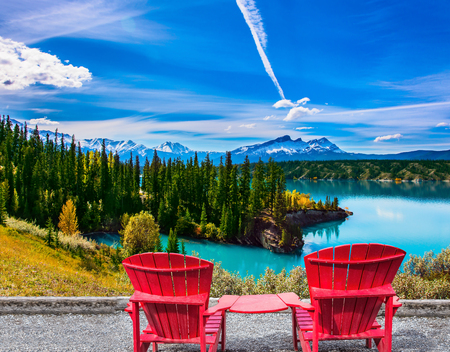 Warm September in the mountains of Canada. Two red comfortable loungers by the Abraham lake with turquoise water. Concept of ecological and active tourism