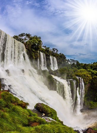 The tropical sun illuminates the seething water of waterfalls Iguazu. Picturesque basaltic ledges form the famous waterfalls. Argentina. The concept of active and exotic tourism Stock Photo