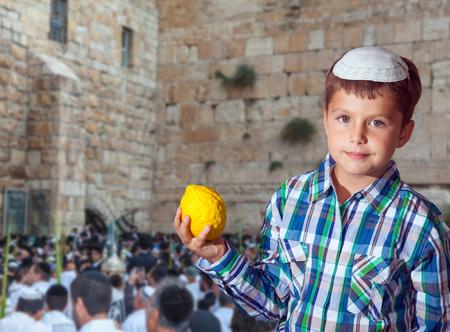 Joodse jongen in witte skullcap, met etrog. Herfst Joodse feestdag Soekot. Mensen in witte Taliths bidden aan de westelijke muur van de tempel