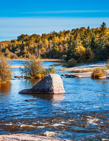 Trend Around the World. The water on the smooth stones of the Winnipeg River. Pinawa Dam Park.  Stock Photo
