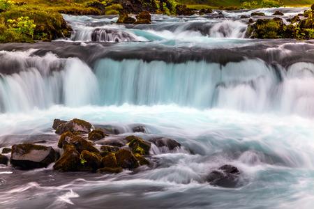 アイスランドの滝を沸騰させる。島の周りの高速道路ナンバーワンに沿って広い絵のように美しい谷。アイスランドの旅行。アクティブで極端な観