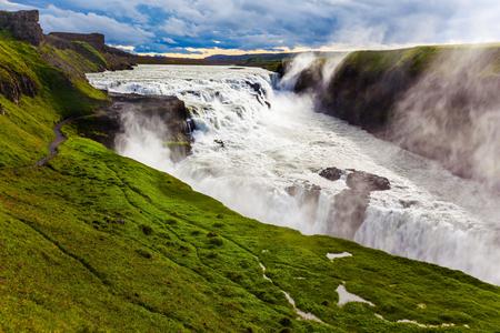 Wassernebel fliegt über Wasserfälle hinweg. Riesige Wassermassen krachen in den Abgrund. Fantastisch malerischer Wasserfall in der isländischen Tundra - Gullfoss. Das Konzept von Extrem und Fototour Standard-Bild - 91996160