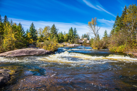 Old dam Pinava. Warm transparent autumn day. Foamy water rifts on smooth stones and low fir-trees on river banks Winnipeg. The concept of ecological and extreme tourism