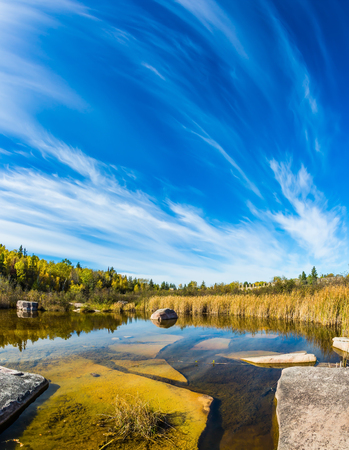 Huge flat stones in riiverbed. Old Pinawa Dam Park, Winnipeg River. Incredible cirrus clouds.  Indian summer in Manitoba, Canada. The concept of recreational tourism