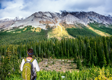 The grandiose landscape of the Rockies of Canada. The experienced woman - tourist with a backpack standing in front of a snow-capped mountain. The concept of active tourism  Stock Photo