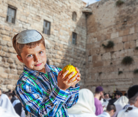 The Western Wall of the Temple. Autumn Jewish holiday Sukkot. Beautiful Jewish boy with green eyes, in white skullcap, with citrus in his hand