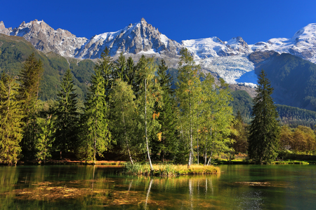 Cozy urban park in Chamonix, Provence. Snowy Alps picturesquely surrounded by evergreen trees and lake Фото со стока