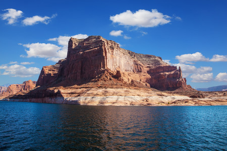 The lake is surrounded by picturesque banks of red sandstone. Scenic huge artificial lake Powell on the Colorado River, USA. Walk on the boat at sunset