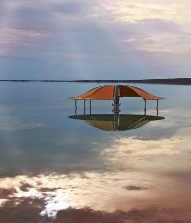 Incredible optical effects at the Dead Sea. The picturesque gazebo for swimmers is reflected in a smooth sea surface.