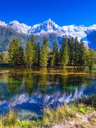 City Park wordt verlicht door de ondergaande zon. Het meer weerspiegelde de met sneeuw bedekte Alpen en groenblijvende sparren. Het bergdorp Chamonix, Haute-Savoie Stockfoto