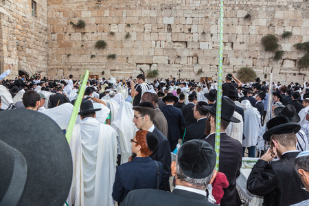 JERUSALEM, ISRAEL - OCTOBER 12, 2014:  Morning autumn Sukkot. Crowd of Jewish worshipers in white wearing prayer shawls. The area of Western Wall of  Temple filled with people
