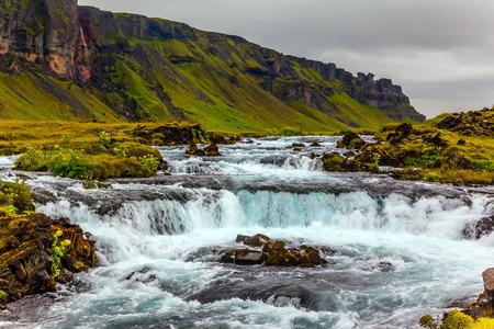 アイスランドの強力なカスケード滝。島の周りの主要道路1番。7月の旅行。アクティブで極端な観光の概念
