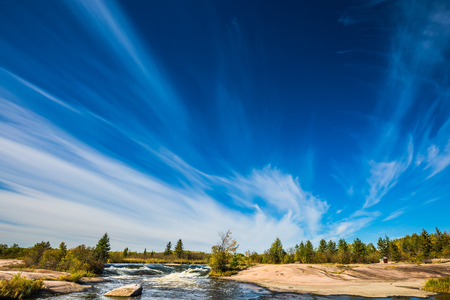 Fabulous cirrus clouds over the Winnipeg River. Old Pinawa Dam Provincial Heritage Park.  The concept of ecological and extreme tourism