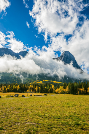 The Three Sisters mountains in the Canadian Rockies. Shining sunny day in Canmore. Mountain peaks are covered with white clouds. Concept of hiking Banco de Imagens