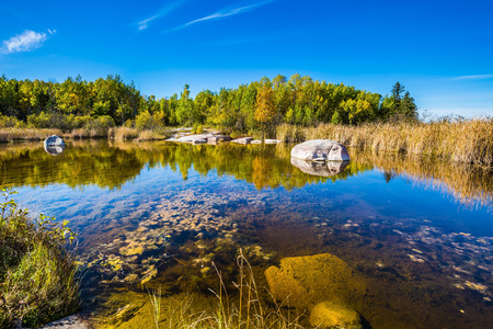 Warm silent day. Old Pinawa Dam Provincial Heritage Park. Yellow autumn grass is reflected in the Winnipeg River. The concept of ecological and recreational tourism Stock Photo