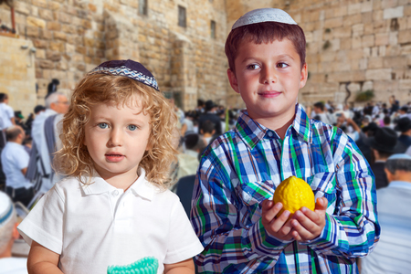 Two beautiful Jewish boys in skull-caps with etrog. Autumn Jewish holiday Sukkot.  The greatest shrine of Judaism is the Western Wall of the Temple