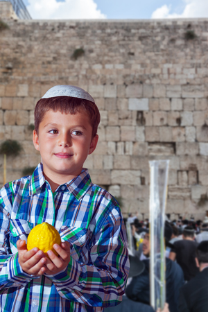 The greatest shrine of Judaism is the Western Wall of the Temple. Autumn Jewish holiday Sukkot. Beautiful Jewish boy with green eyes, in white skullcap, with etrog Stock Photo