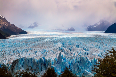 Argentine province of Santa Cruz. The spectacular glacier Perito Moreno in the Argentine part of Patagonia. The concept of ecological and extreme tourism. The cloudy sky covers the horizon