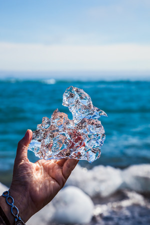 Transparent piece of ice in hand on background of ocean. The concept of extreme northern tourism. Iceland, Jokulsarlon. Icy Atlantic coast Stock Photo