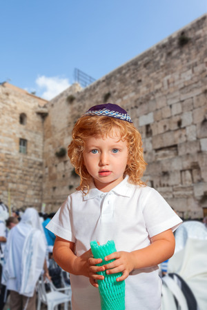 Autumn Jewish holiday Sukkot. Lovely blonde boy with blue eyes in a skullcap. The Western Wall of the Temple