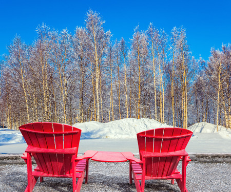 Bright winter frosty day in the Arctic. Large and comfortable red plastic chaise lounges for relaxing. The concept of extreme and ecotourism tourism