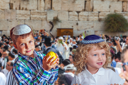 The Western Wall of the Temple. Autumn Jewish holiday Sukkot. Two beautiful Jewish boys in skull-caps with etrog Stock Photo
