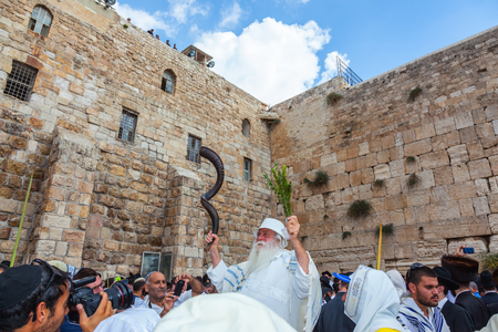 JERUSALEM, ISRAEL - OCTOBER 12, 2014: The area in front of Western Wall of  Temple filled with people. Elderly religious Jew with a Shofar. Morning autumn Sukkot Editorial
