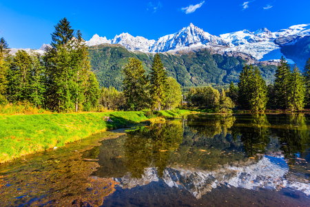 The lake reflects the snowy mountains, the forest and the blue sky. Chamonix City Park is illuminated by sunset. Sunny autumn day in the French Alps. Concept of active winter tourism