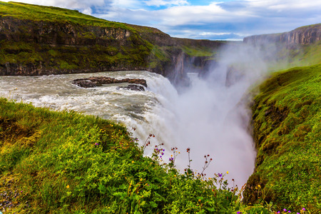 Huge masses of water crash into the abyss. Water fog fly up over falls. The most picturesque waterfall in Iceland - Gullfoss. The concept of extreme and phototour Stok Fotoğraf