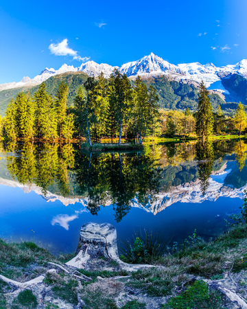 Park in the mountain resort of Chamonix, at the foot of Mont Blanc. Snowy peaks of the Alps are beautifully reflected in the lake. Concept of active and ecotourism Stock Photo