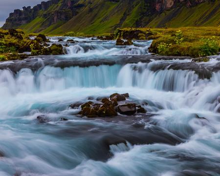 アイスランドの強力なカスケード滝。島の周りのハイウェイ1に沿って広い絵のように美しい谷。7月の旅行。アクティブで極端な観光の概念
