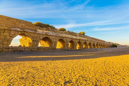 High aqueduct, built under the reign of Herod the Great. Concept of active, ecological and historical tourism. Fantastic sunset on the Mediterranean coast in Caesarea Stock Photo