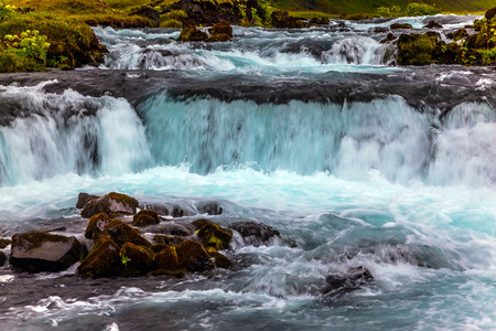 Wide picturesque valley along highway number one around the island. Travel in Iceland. Powerful cascading waterfalls. Concept of active and extreme tourism