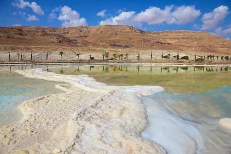 Path from the salt winds picturesquely in salt water. Israeli coast of the Dead Sea